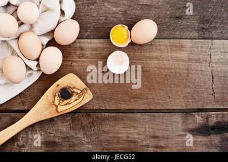 Farm fresh organic brown chicken eggs from free range chickens with an old olive wood antique spatula over a rustic - Stock Photo