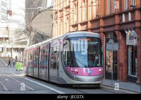 A Midland Metro Urbos 3 tram in Stephenson Street, central Birmingham, England. Entrance to New Street Rail Station - Stock Photo