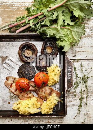 full English style breakfast with black pudding bacon mushrooms and eggs - Stock Photo