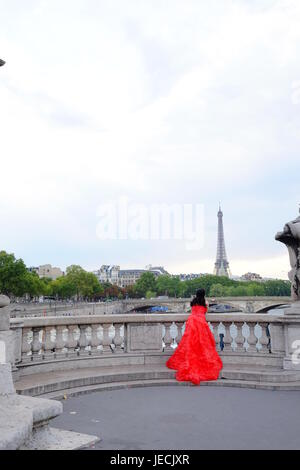 A woman in a long red dress or gown looking at the Eiffel Tower in Paris - Stock Photo