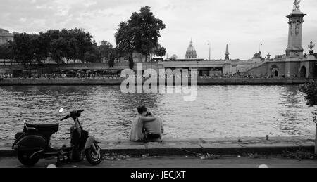 Romantic young couple embrace on the bank of the River Seine in Paris with their scooter nearby - Stock Photo