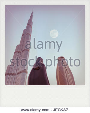 'Together' Statue with the moon and Burj Khalifa in a frame looking like a Polaroid support with vintage effect - Stock Photo