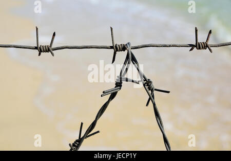 Fragment of the barbed wire fencing of the entrance to the sea, summer day - Stock Photo