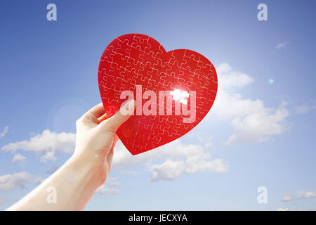 Hand, jigsaw puzzle, heart form, red, incompletely, hole, cloudy sky, back light, - Stock Photo