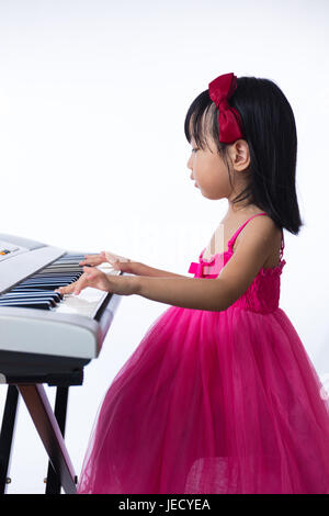 Asian Chinese little girl playing electric piano keyboard in the living room at home. - Stock Photo