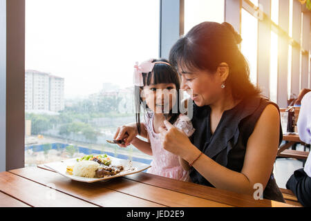 Asian Chinese mother and daughter eating steak in the restaurant. - Stock Photo