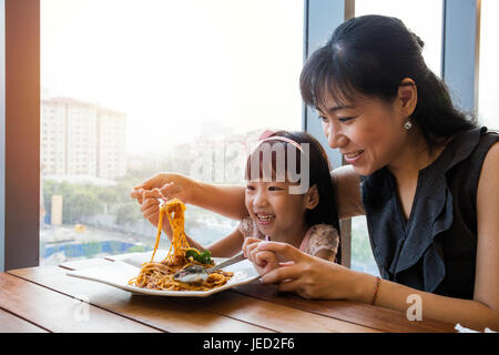 Asian Chinese mother and daughter eating spaghetti bolognese in the restaurant. - Stock Photo