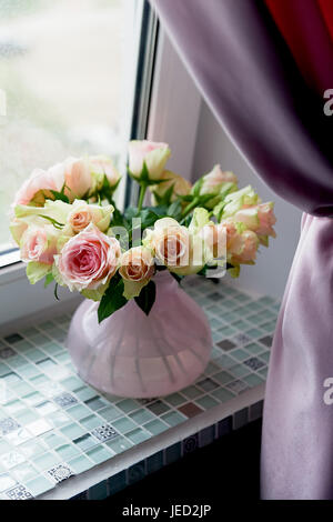 Bouquet of pink roses on the windowsill,in a pink vase. the atmosphere of coziness - Stock Photo