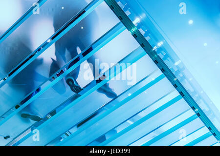 Modern glass staircase with person walking on it - Stock Photo
