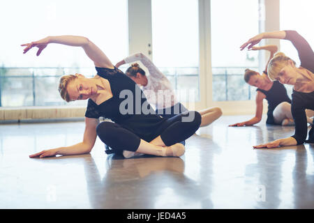 Group of mature ballerinas sitting on floor with hands up doing gymnastics in ballet class. - Stock Photo