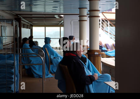 Passengers wrap up in blankets as they watch a film on the seascreen on board the Cruise ship Azura, P&O cruises - Stock Photo