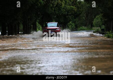 Huangshan, China's Anhui Province. 24th June, 2017. A car moves slowly on a waterlogged road connecting Qiyun Mountain - Stock Photo