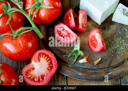 Tomatoes and white Greek cheese on a wooden board. - Stock Photo