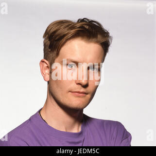 Portrait of a young man in a purple t shirt - Stock Photo