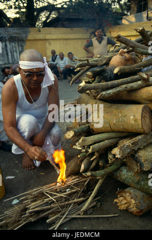 India, Calcutta, Hindu cremation. Son lighting his father s funeral pyre under partly covered body. - Stock Photo