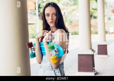 Closeup portrait of pretty beautiful girl in white t-shirt and short denim overall holding short skate board. Urban - Stock Photo
