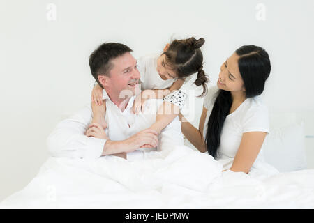 Family with beautiful mother and handsome father with cute little daughter are talking and smiling while spending - Stock Photo