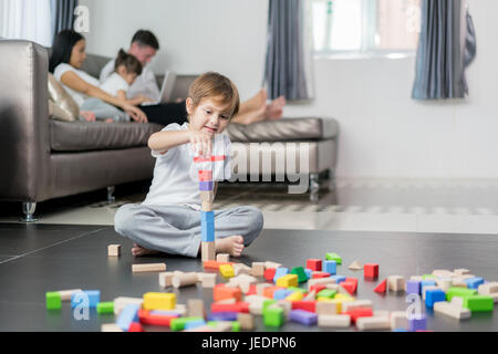 Asian boy playing wood toy in living room with father, mother and daughter in background. Happy family. - Stock Photo