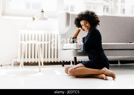Young woman sitting on floor leaning on couch - Stock Photo