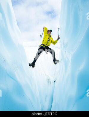Ice climber climbing out of a crevasse on the Matanuska Glacier in Alaska. He is soloing up the span and stemming - Stock Photo