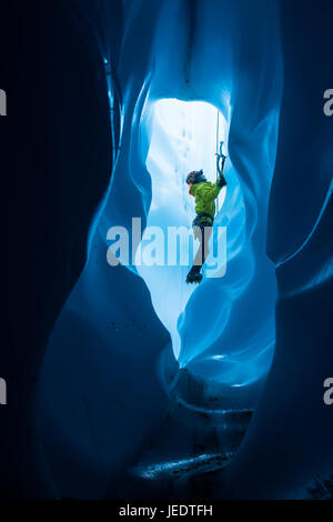 An ice climber inside of a large ice tunnel in the bottom of a moulin. He is climbing out toward the top entrance to the hole