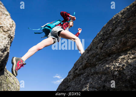 Spain, Madrid, young woman jumping between rocks during a trekking day - Stock Photo