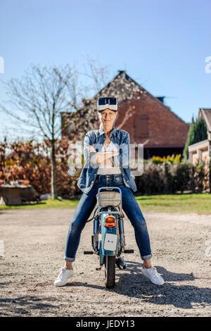 Woman sitting backwards on vintage motorcycle wearing VR glasses - Stock Photo