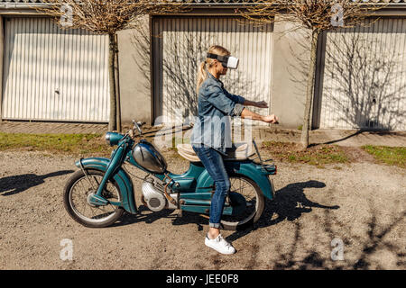 Woman with vintage motorcycle wearing VR glasses - Stock Photo