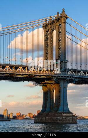 Detail of the Manhattan Bridge east tower over the East River at sunset. New York City Stock Photo