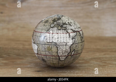 A sphere or globe of the world that has a vintage and old fashioned look on a wooden background. - Stock Photo