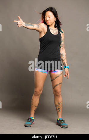 Athletic young asian woman with tattoos dressed in a black tank top and colored gym shorts smiles - Stock Photo