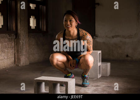 Athletic young asian woman with tattoos doing body weight exercises in a concrete warehouse with cinder blocks - Stock Photo