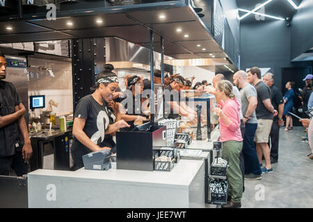 Employees construct a pizza right before the customers' eyes in assembly line fashion on opening day of &pizza in - Stock Photo