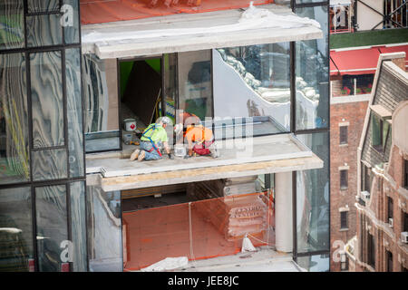 Construction workers on the balcony of an unfinished development in Midtown Manhattan in New York on Wednesday, - Stock Photo