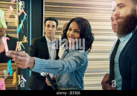 Creative group of business people brainstorming putting sticky notes on glass wall in office - Stock Photo