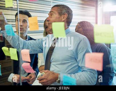 Half body portrait of businessman sticking note on glass, colleagues in background - Stock Photo