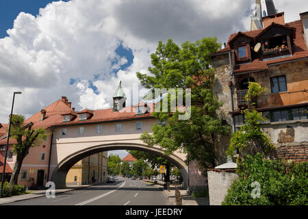 Building arch with rooms and clock tower over four lane Karlovska road with St. James Catholic church belfry Ljubljana - Stock Photo