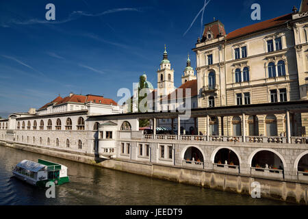 Tour boat on the Ljubljanica river canal at Kresija Building St Nicholas Cathedral at Pogacar Square and Central - Stock Photo