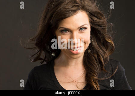Young caucasian woman with brown hair and a black top smiles at the viewer - Stock Photo