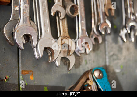 different wrenches hanging on wall - Stock Photo