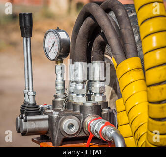 Control levers and pressure control unit of the hydraulic machine closeup - Stock Photo