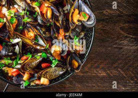 A closeup of a skillet of marinara mussels, shot from above on a dark rustic background texture with a place for - Stock Photo
