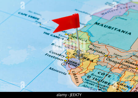 Photo of Sierra Leone marked by red flag in holder. Country on African continent. - Stock Photo