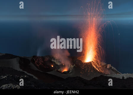 Strong strombolian volcanic eruption from Stromboli volcano (Eolian Islands, Lipari, Italy) at night, craters illuminated - Stock Photo