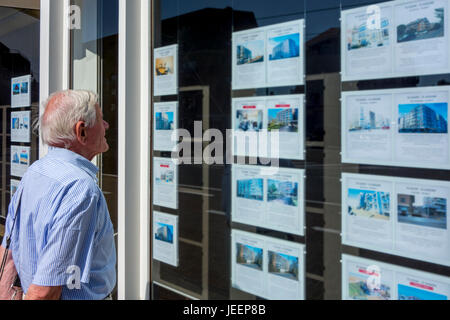 Elderly man looking at prices of flats / apartments for sale in display window of real estate / property agency - Stock Photo