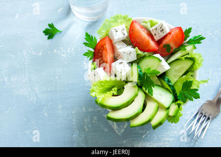 Green salad with sliced avocado, tomatoes, cucumbers and greek feta cheese on wooden table. Healthy diet vegan vegetarian - Stock Photo