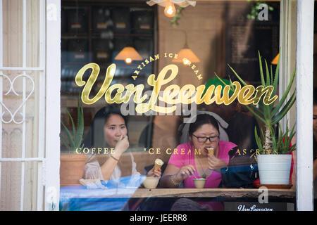 Asian tourists eating ice cream at Van Leeuwen Artisan Ice Cream, East Village, Manhattan, New York - Stock Photo