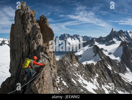 A climber on the traverse of the Aiguille d'Entrees in the Mont Blanc massif - Stock Photo