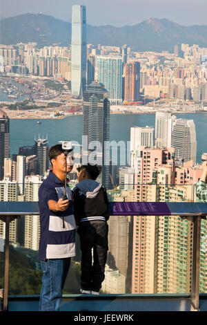 Vertical view of a man taking a selfie from up the Peak in Hong Kong, China. - Stock Photo