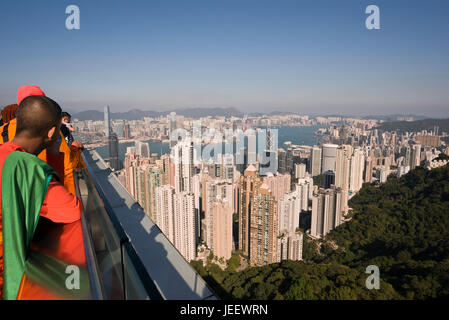 Horizontal view of Buddhist monks enjoying the view from up the Peak in Hong Kong, China. - Stock Photo